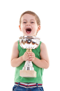 picture of a small kid winning a trophy, over white